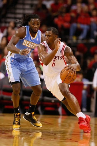 Nov 16, 2013; Houston, TX, USA; Houston Rockets forward Terrence Jones (6) moves the ball against the defense of Denver Nuggets forward Kenneth Faried (left) during the second half at Toyota Center. The Rockets won 122-111. Mandatory Credit: Soobum Im-USA TODAY Sports