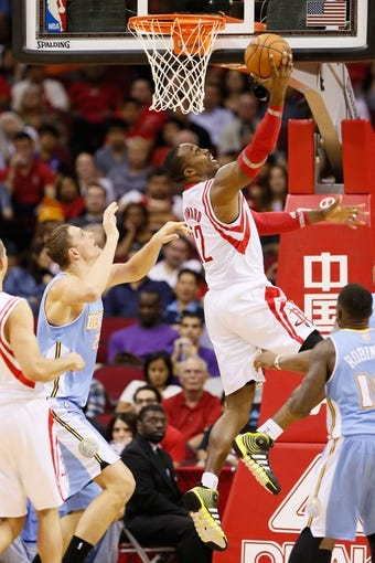 Nov 16, 2013; Houston, TX, USA; Houston Rockets center Dwight Howard (12) drives to the basket past Denver Nuggets center Timofey Mozgov (left) during the second half at Toyota Center. The Rockets won 122-111. Mandatory Credit: Soobum Im-USA TODAY Sports