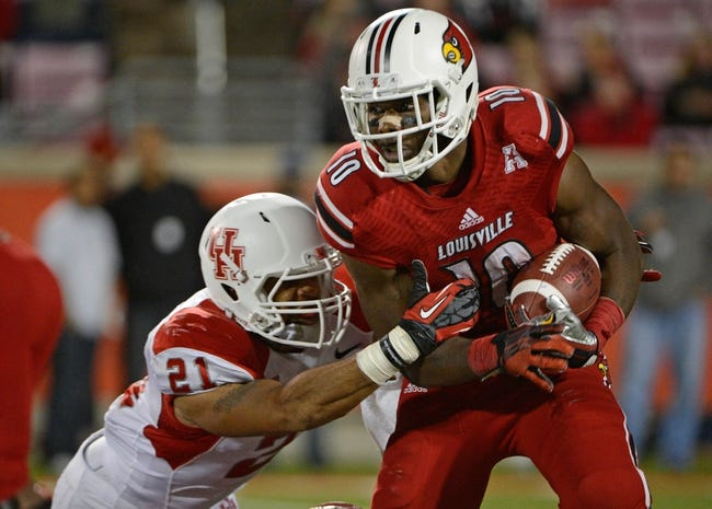 Nov 16, 2013; Louisville, KY, USA; Louisville Cardinals running back Dominique Brown (10) runs the ball against Houston Cougars defensive end Eric Eiland (21) during the second half of play at Papa John's Cardinal Stadium. Louisville defeated Houston 20-13.  Mandatory Credit: Jamie Rhodes-USA TODAY Sports