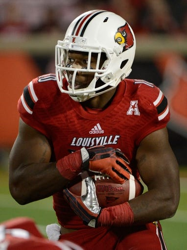 Nov 16, 2013; Louisville, KY, USA; Louisville Cardinals running back Dominique Brown (10) runs the ball against the Houston Cougars during the second half of play at Papa John's Cardinal Stadium. Louisville defeated Houston 20-13.  Mandatory Credit: Jamie Rhodes-USA TODAY Sports
