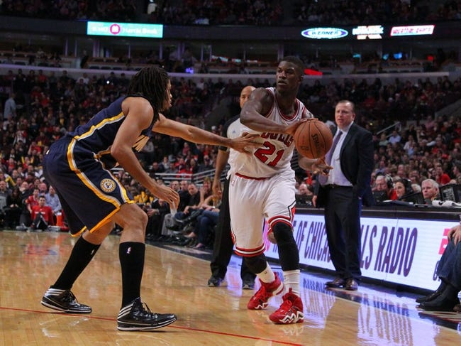 Nov 16, 2013; Chicago, IL, USA; Chicago Bulls shooting guard Jimmy Butler (21) passes around Indiana Pacers small forward Chris Copeland (22) during the second half at  the United Center. Chicago won 110-94. Mandatory Credit: Dennis Wierzbicki-USA TODAY Sports