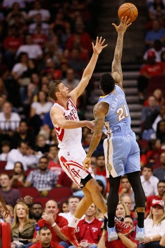 Nov 16, 2013; Houston, TX, USA; Houston Rockets forward Chandler Parsons (25) takes a shot over Denver Nuggets forward Wilson Chandler (21) during the second half at Toyota Center. The Rockets won 122-111. Mandatory Credit: Soobum Im-USA TODAY Sports