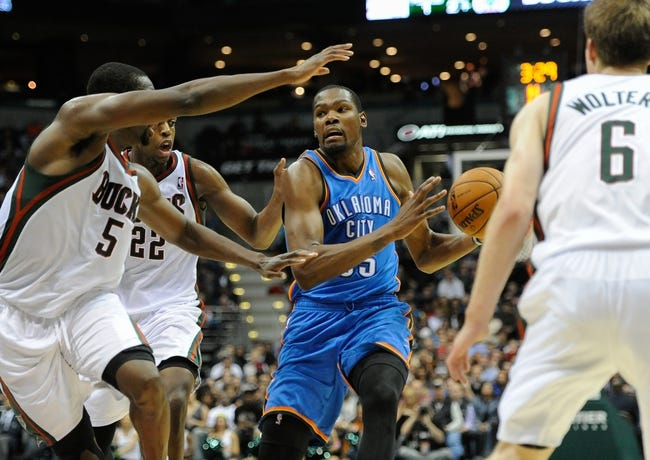 Nov 16, 2013; Milwaukee, WI, USA;   Oklahoma City Thunder forward Kevin Durant (35) drives for the basket between Milwaukee Bucks forward Ekpe Udoh (5), forward Khris Middleton (22), and guard Nate Wolters (6) in the 4th quarter at BMO Harris Bradley Center. Mandatory Credit: Benny Sieu-USA TODAY Sports