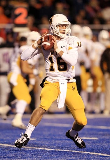 Nov 16, 2013; Boise, ID, USA; Wyoming Cowboys quarterback Brett Smith (16) sets up to pass down field during first half of against the Boise State Broncos at Bronco Stadium. Mandatory Credit: Brian Losness-USA TODAY Sports