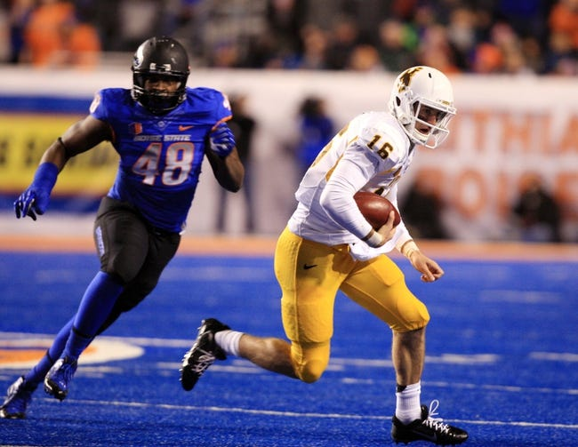 Nov 16, 2013; Boise, ID, USA; Wyoming Cowboys quarterback Brett Smith (16) attempts to elude Boise State Broncos defensive end Kharyee Marshall (48) during first half of play verses the Boise State Broncos at Bronco Stadium. Mandatory Credit: Brian Losness-USA TODAY Sports