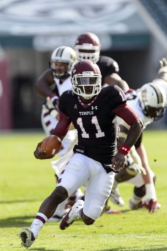 Nov 16, 2013; Philadelphia, PA, USA; Temple Owls quarterback P.J. Walker (11) carries the ball during the first quarter against the UCF Knights at Lincoln Financial Field. UCF defeated Temple 39-36. Mandatory Credit: Howard Smith-USA TODAY Sports
