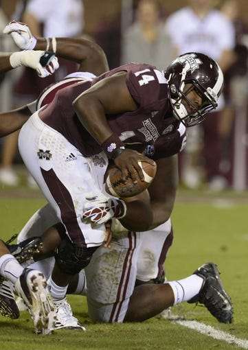 Nov 16, 2013; Starkville, MS, USA;  Mississippi State Bulldogs quarterback Damian Williams (14) gets sacked for a loss by Alabama Crimson Tide defensive lineman A'Shawn Robinson (86) during the fourth quarter at Davis Wade Stadium. Alabama defeated Mississippi State 20-7. Mandatory Credit: John David Mercer-USA TODAY Sports