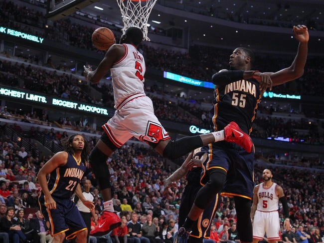Nov 16, 2013; Chicago, IL, USA; Chicago Bulls small forward Luol Deng (9) scores past Indiana Pacers center Roy Hibbert (55) during the second half at  the United Center. Chicago won 110-94. Mandatory Credit: Dennis Wierzbicki-USA TODAY Sports