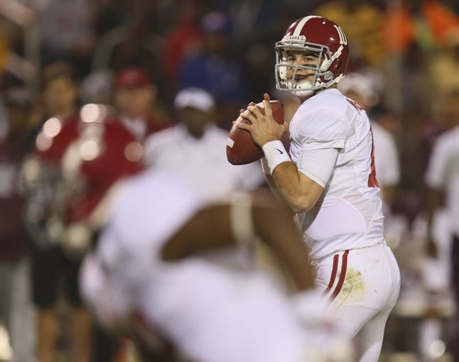 Nov 16, 2013; Starkville, MS, USA; Alabama Crimson Tide quarterback AJ McCarron (10) drops back to pass the ball during the game against the Mississippi State Bulldogs at Davis Wade Stadium. Alabama Crimson Tide defeat the Mississippi State Bulldogs with a score of 20-7.  Mandatory Credit: Spruce Derden-USA TODAY Sports