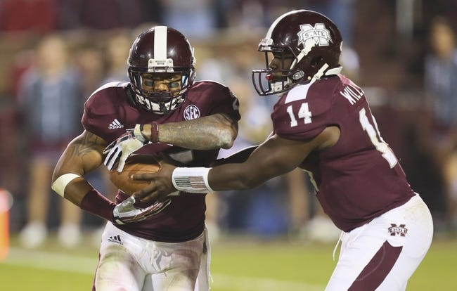Nov 16, 2013; Starkville, MS, USA; Mississippi State Bulldogs quarterback Damian Williams (14) hands the ball off to running back LaDarius Perkins (27) during the game against the Alabama Crimson Tide at Davis Wade Stadium. Alabama Crimson Tide defeat the Mississippi State Bulldogs with a score of 20-7.  Mandatory Credit: Spruce Derden-USA TODAY Sports