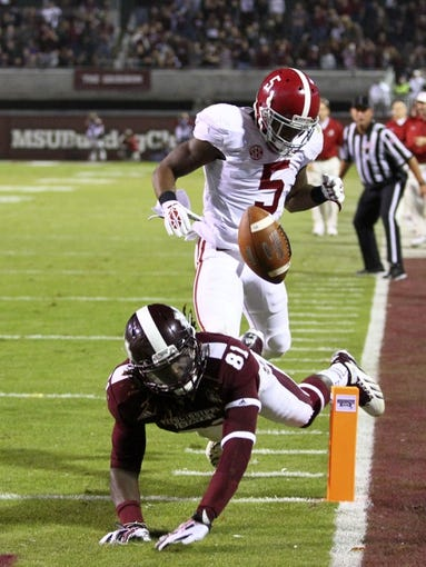Nov 16, 2013; Starkville, MS, USA; Mississippi State Bulldogs wide receiver De'Runnya Wilson (81) jumps for the pass while guarded by Alabama Crimson Tide wide receiver Cyrus Jones (5) during the game at Davis Wade Stadium. Alabama Crimson Tide defeat the Mississippi State Bulldogs with a score of 20-7.  Mandatory Credit: Spruce Derden-USA TODAY Sports
