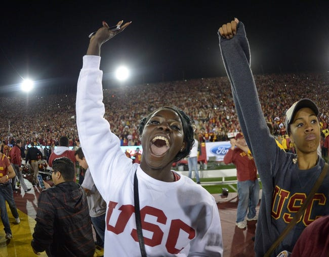 Nov 16, 2013; Los Angeles, CA, USA; Southern California Trojans fan Akawkaw Ndipagbor celebrates at the end of the game against the Stanford Cardinal at Los Angeles Memorial Coliseum. USC defeated Stanford 20-17. Mandatory Credit: Kirby Lee-USA TODAY Sports