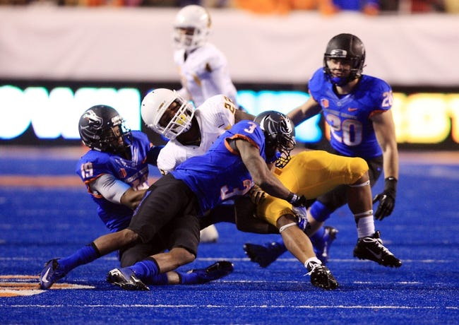 Nov 16, 2013; Boise, ID, USA; Wyoming Cowboys running back Tedder Easton (22) is upended by Boise State Broncos cornerback Cleshawn Page (3) and cornerback Mercy Maston (19) during the second half of play at Bronco Stadium. Boise State beat Wyoming 48-7. Mandatory Credit: Brian Losness-USA TODAY Sports