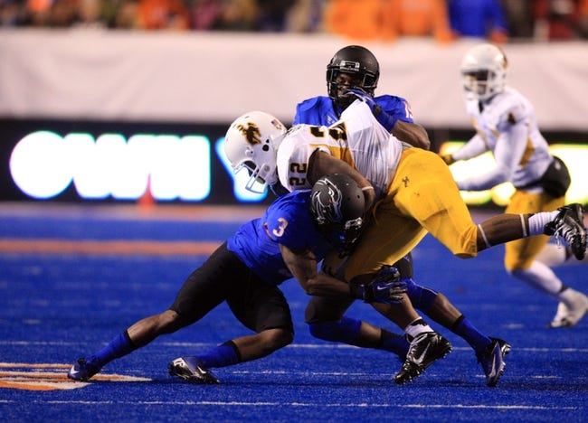 Nov 16, 2013; Boise, ID, USA; Wyoming Cowboys running back Tedder Easton (22) is upended by Boise State Broncos cornerback Cleshawn Page (3) and cornerback Mercy Maston (19) during the second half at Bronco Stadium. Boise State beat Wyoming 48-7. Mandatory Credit: Brian Losness-USA TODAY Sports