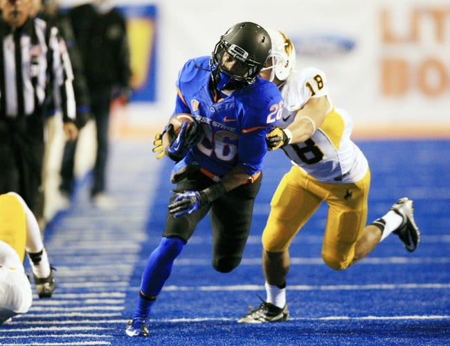 Nov 16, 2013; Boise, ID, USA; Boise State Broncos running back Devan Demas (26) runs down the sidelines as Wyoming Cowboys safety Xavier Lewis (18) attempts to catch him during the second half  at Bronco Stadium. Boise State defeated Wyoming 48-7. Mandatory Credit: Brian Losness-USA TODAY Sports