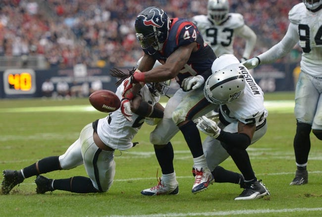 Nov 17, 2013; Houston, TX, USA; Oakland Raiders safety Charles Woodson (24) and cornerback Mike Jenkins (21) force a fumble by Houston Texans running back Ben Tate (44) in the fourth quarter at Reliant Stadium. The Raiders defeated the Texans 28-23. Mandatory Credit: Kirby Lee-USA TODAY Sports