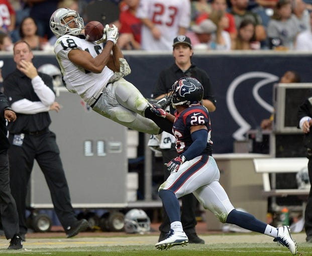 Nov 17, 2013; Houston, TX, USA; Oakland Raiders receiver Andre Holmes (18) is defended by Houston Texans cornerback Brandon Harris (26) at Reliant Stadium. The Raiders defeated the Texans 28-23. Mandatory Credit: Kirby Lee-USA TODAY Sports