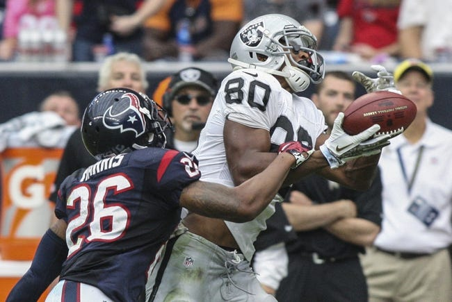 Nov 17, 2013; Houston, TX, USA; Oakland Raiders wide receiver Rod Streater (80) makes a reception during the third quarter as Houston Texans defensive back Brandon Harris (26) defends at Reliant Stadium. The Raiders defeated the Texans 28-23. Mandatory Credit: Troy Taormina-USA TODAY Sports