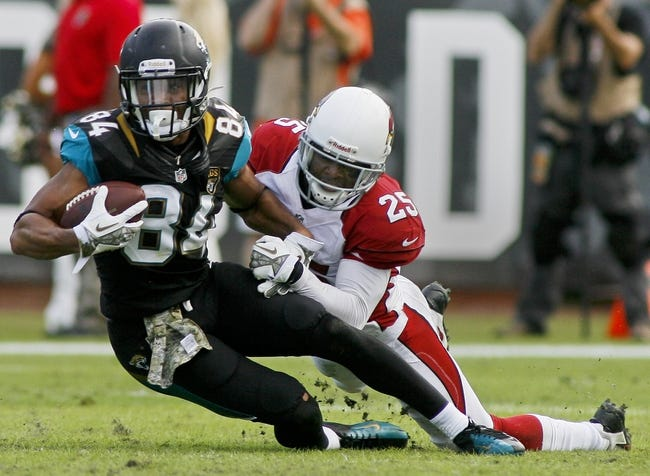 Nov 17, 2013; Jacksonville, FL, USA; Jacksonville Jaguars wide receiver Cecil Shorts III (84) is tackled by Arizona Cardinals cornerback Jerraud Powers (25) after catching a pass in the fourth quarter of their game at EverBank Field. The Arizona Cardinals beat the Jacksonville Jaguars 27-14. Mandatory Credit: Phil Sears-USA TODAY Sports