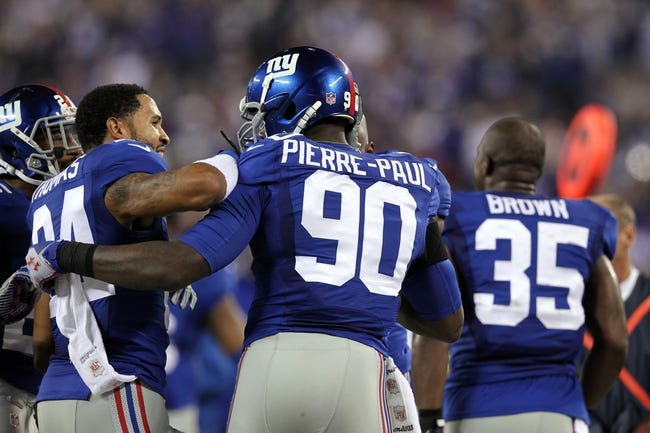 Nov 17, 2013; East Rutherford, NJ, USA; New York Giants defensive end Jason Pierre-Paul (90) celebrates his interception return for a touchdown with New York Giants corner back Terrell Thomas (24) during the fourth quarter of a game against the Green Bay Packers at MetLife Stadium. Mandatory Credit: Brad Penner-USA TODAY Sports