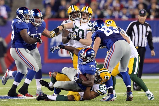 Nov 17, 2013; East Rutherford, NJ, USA; New York Giants running back Andre Brown (35) is tackled by Green Bay Packers linebacker Brad Jones (59) during the fourth quarter of a game at MetLife Stadium. Mandatory Credit: Brad Penner-USA TODAY Sports