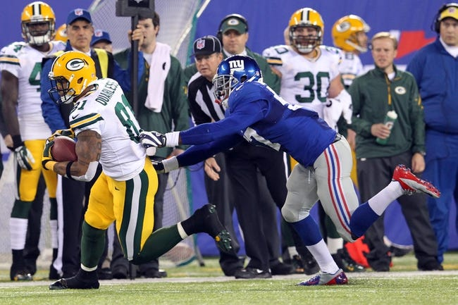 Nov 17, 2013; East Rutherford, NJ, USA; Green Bay Packers tight end Andrew Quarless (81) runs with the ball past New York Giants linebacker Jacquian Williams (57) during the third quarter of a game at MetLife Stadium. Mandatory Credit: Brad Penner-USA TODAY Sports