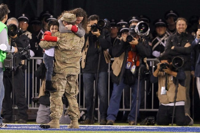 Nov 17, 2013; East Rutherford, NJ, USA; Air force tech sgt David Brenhuber (Joint Base McGuire-Dix-Lakehurst) surprises his wife Tammy and daughter Alexis (4yo) during the second quarter of a game between the New York Giants and the Green Bay Packers at MetLife Stadium. Brenhuber recently returned from Bagram Airfield in Afghanistan and his family didn't know they would be reunited with him during the game. Mandatory Credit: Brad Penner-USA TODAY Sports