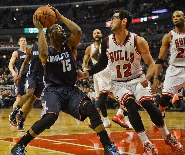 Nov 18, 2013; Chicago, IL, USA; Charlotte Bobcats point guard Kemba Walker (15)shoots the ball against Chicago Bulls shooting guard Kirk Hinrich (12) during the second quarter of their game against the Chicago Bulls at the United Center. Mandatory Credit: Matt Marton-USA TODAY Sports