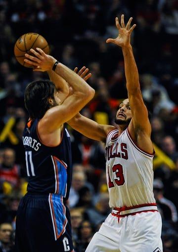 Nov 18, 2013; Chicago, IL, USA; Charlotte Bobcats power forward Josh McRoberts (11) passes against Chicago Bulls center Joakim Noah (13) during the second half of their game at the United Center. The Bulls won 86-81. Mandatory Credit: Matt Marton-USA TODAY Sports