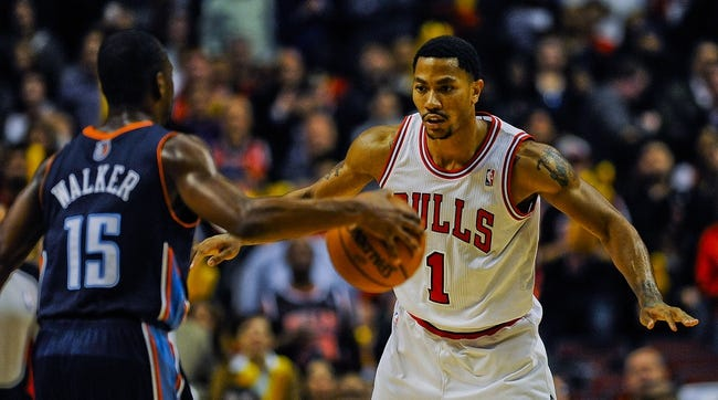 Nov 18, 2013; Chicago, IL, USA; Charlotte Bobcats point guard Kemba Walker (15) dribbles near Chicago Bulls point guard Derrick Rose (1) during the second half of their game at the United Center. The Bulls won 86-81. Mandatory Credit: Matt Marton-USA TODAY Sports
