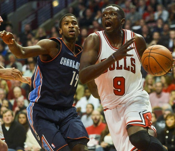 Nov 18, 2013; Chicago, IL, USA; Chicago Bulls small forward Luol Deng (9) dribbles the ball around Charlotte Bobcats small forward Michael Kidd-Gilchrist (14) during the second half at the United Center. The Bulls won 86-81. Mandatory Credit: Matt Marton-USA TODAY Sports