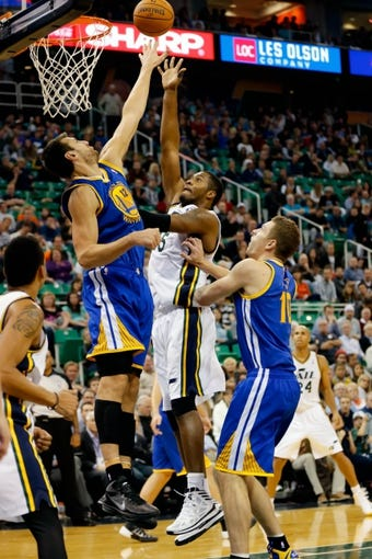 Nov 18, 2013; Salt Lake City, UT, USA; Golden State Warriors center Andrew Bogut (12) blocks a shot by Utah Jazz point guard John Lucas III (5) during the fourth quarter at EnergySolutions Arena. Golden State Warriors won 98-87. Mandatory Credit: Chris Nicoll-USA TODAY Sports