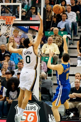 Nov 18, 2013; Salt Lake City, UT, USA; Golden State Warriors shooting guard Klay Thompson (11) shoots the ball over Utah Jazz center Enes Kanter (0) during the fourth quarter at EnergySolutions Arena. Golden State Warriors won 98-87. Mandatory Credit: Chris Nicoll-USA TODAY Sports
