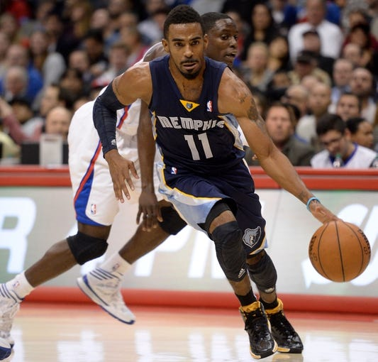 Nov 18, 2013; Los Angeles, CA, USA; Memphis Grizzlies point guard Mike Conley (11) drives to the basket past Los Angeles Clippers point guard Darren Collison (2) during first half action at Staples Center. Mandatory Credit: Robert Hanashiro-USA TODAY Sports