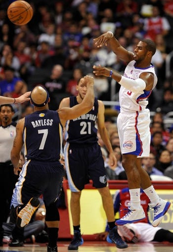 Nov 18, 2013; Los Angeles, CA, USA;  Los Angeles Clippers point guard Chris Paul (3) passes to a teammate over Memphis Grizzlies point guard Jerryd Bayless (7) during first half action at Staples Center. Mandatory Credit: Robert Hanashiro-USA TODAY Sports