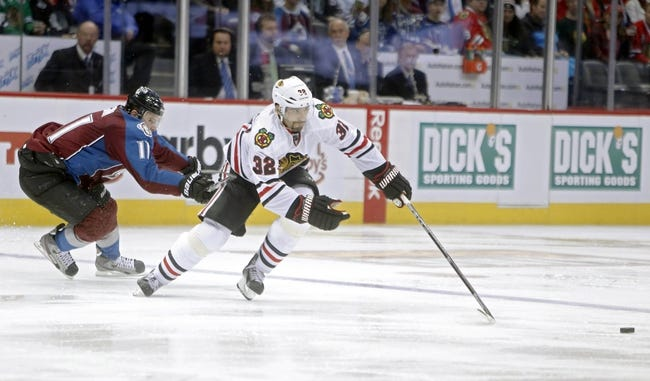 Nov 19, 2013; Denver, CO, USA; Chicago Blackhawks defenseman Michal Rozsival (32) reaches for the puck in front of Colorado Avalanche left wing Jamie McGinn (11) during the third period at Pepsi Center. The Avalanche won 5-1. Mandatory Credit: Chris Humphreys-USA TODAY Sports