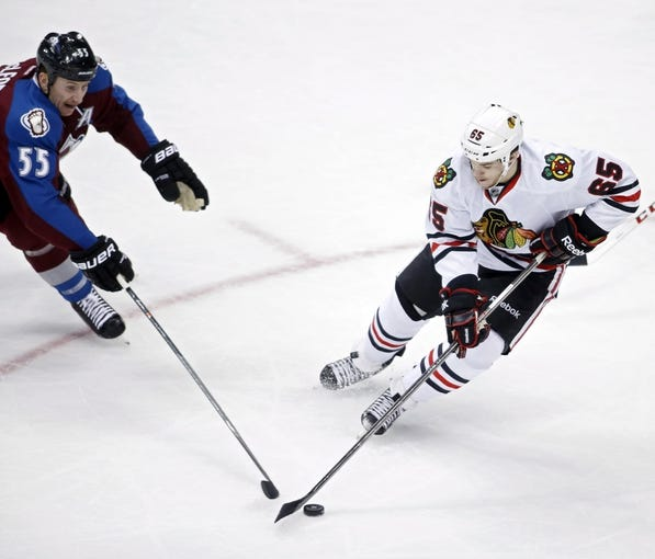 Nov 19, 2013; Denver, CO, USA; Colorado Avalanche left wing Cody McLeod (55) and Chicago Blackhawks center Andrew Shaw (65) battle for the puck during the first period at Pepsi Center. Mandatory Credit: Chris Humphreys-USA TODAY Sports