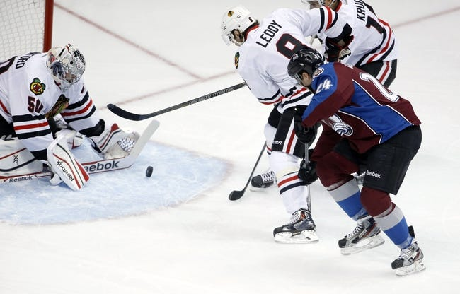 Nov 19, 2013; Denver, CO, USA; Chicago Blackhawks goalie Corey Crawford (50) blocks a shot from Colorado Avalanche center Marc-Andre Cliche (24) during the first period at Pepsi Center. Mandatory Credit: Chris Humphreys-USA TODAY Sports