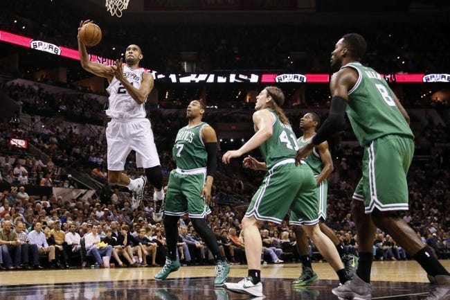 Nov 20, 2013; San Antonio, TX, USA; San Antonio Spurs forward Tim Duncan (top) is fouled by Boston Celtics forward Jared Sullinger (7)  while driving to the basket during the second half at AT&T Center. The Spurs won 104-93. Mandatory Credit: Soobum Im-USA TODAY Sports