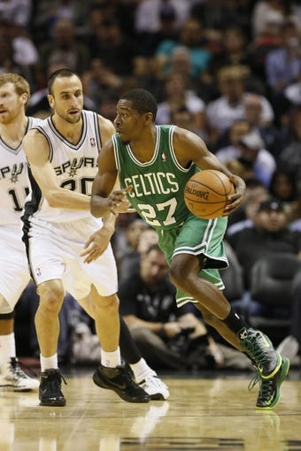 Nov 20, 2013; San Antonio, TX, USA; Boston Celtics guard Jordan Crawford (27) moves the ball against the defense of San Antonio Spurs guard Manu Ginobili (left) during the second half at AT&T Center. The Spurs won 104-93. Mandatory Credit: Soobum Im-USA TODAY Sports