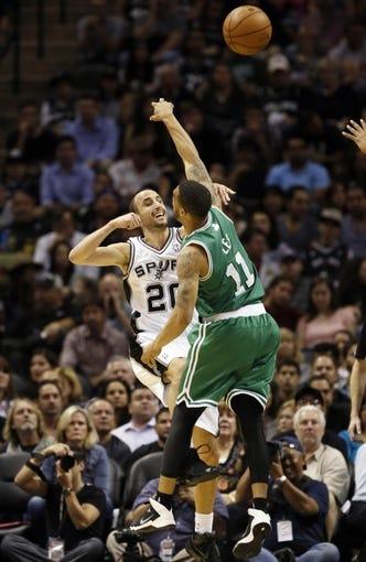 Nov 20, 2013; San Antonio, TX, USA; San Antonio Spurs guard Manu Ginobili (20) passes the ball over Boston Celtics guard Courtney Lee (11) during the first half at AT&T Center. Mandatory Credit: Soobum Im-USA TODAY Sports