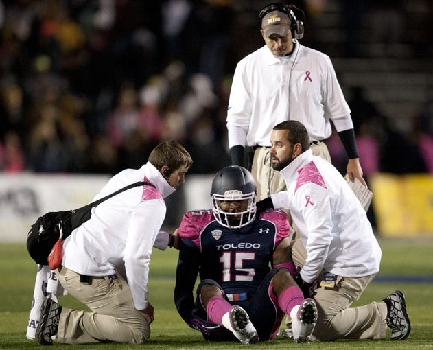 Nov 20, 2013; Toledo, OH, USA; Toledo Rockets defensive end Jayrone Elliott (15) gets medical attention during the fourth quarter as head coach Matt Campbell stands behind him against the Northern Illinois Huskies at Glass Bowl. The Huskies beat the Rockets 35-17. Mandatory Credit: Raj Mehta-USA TODAY Sports