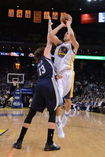 November 20, 2013; Oakland, CA, USA; Golden State Warriors shooting guard Klay Thompson (11) shoots the ball against Memphis Grizzlies small forward Mike Miller (13) during the fourth quarter at Oracle Arena. The Grizzlies defeated the Warriors 88-81 in overtime. Mandatory Credit: Kyle Terada-USA TODAY Sports