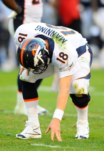 Nov 10, 2013; San Diego, CA, USA; Denver Broncos quarterback Peyton Manning (18) after being hit on a play during the second half against the San Diego Chargers at Qualcomm Stadium. The Broncos won 28-20. Mandatory Credit: Christopher Hanewinckel-USA TODAY Sports