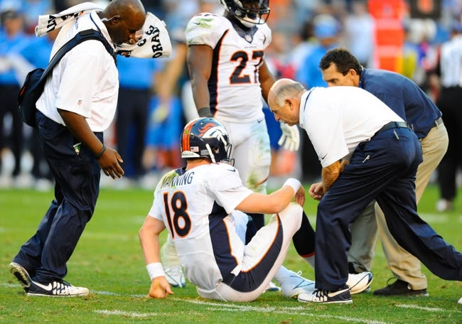 Nov 10, 2013; San Diego, CA, USA; Denver Broncos quarterback Peyton Manning (18) is looked at by members of the medical staff after being hit on a pass play during the second half against the San Diego Chargers at Qualcomm Stadium. The Broncos won 28-20. Mandatory Credit: Christopher Hanewinckel-USA TODAY Sports