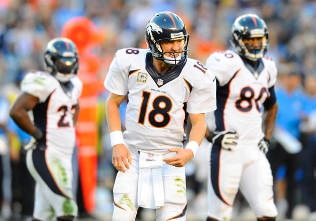 Nov 10, 2013; San Diego, CA, USA; Denver Broncos quarterback Peyton Manning (18) signals to the sidelines for a trainer after being hit on a play during the second half against the San Diego Chargers at Qualcomm Stadium. The Broncos won 28-20. Mandatory Credit: Christopher Hanewinckel-USA TODAY Sports