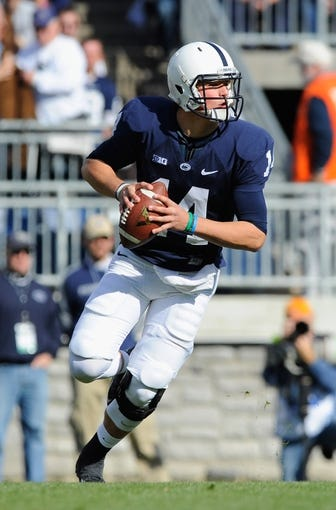 Nov 16, 2013; University Park, PA, USA; Penn State Nittany Lions quarterback Christian Hackenberg (14) rolls out of the pocket against the Purdue Boilermakers during the first quarter at Beaver Stadium.  Penn State defeated Purdue  45-21.  Mandatory Credit: Rich Barnes-USA TODAY Sports