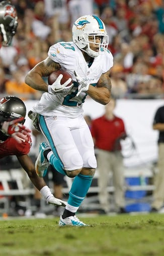Nov 11, 2013; Tampa, FL, USA; Miami Dolphins safety Jimmy Wilson (27) runs with the ball after he intercepted it against the Tampa Bay Buccaneers  during the second half at Raymond James Stadium. Tampa Bay Buccaneers defeated the Miami Dolphins 22-19. Mandatory Credit: Kim Klement-USA TODAY Sports