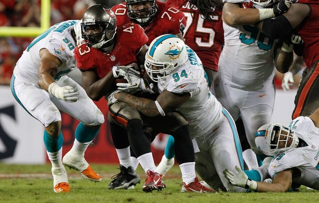 Nov 11, 2013; Tampa, FL, USA; Miami Dolphins defensive tackle Randy Starks (94) tackles Tampa Bay Buccaneers running back Bobby Rainey (43) during the second half at Raymond James Stadium. Mandatory Credit: Kim Klement-USA TODAY Sports