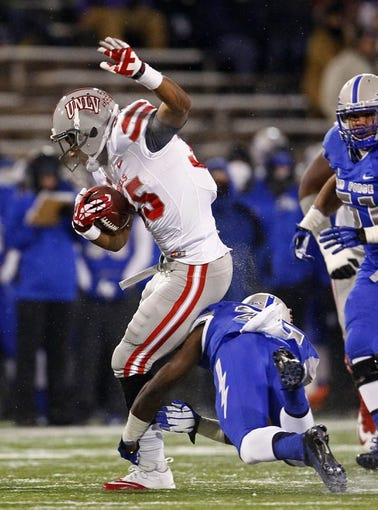 Nov 21, 2013; Colorado Springs, CO, USA; UNLV Rebels running back Tim Cornett (35) runs through the tackle of Air Force Falcons defensive back Christian Spears (21) in the first quarter at Falcon Stadium. Mandatory Credit: Isaiah J. Downing-USA TODAY Sports